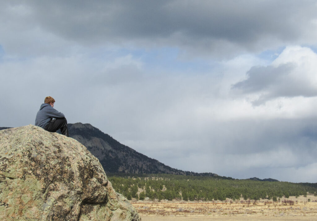 Teenage Boy looks out over Moraine Valley in Rocky Mountain National Park