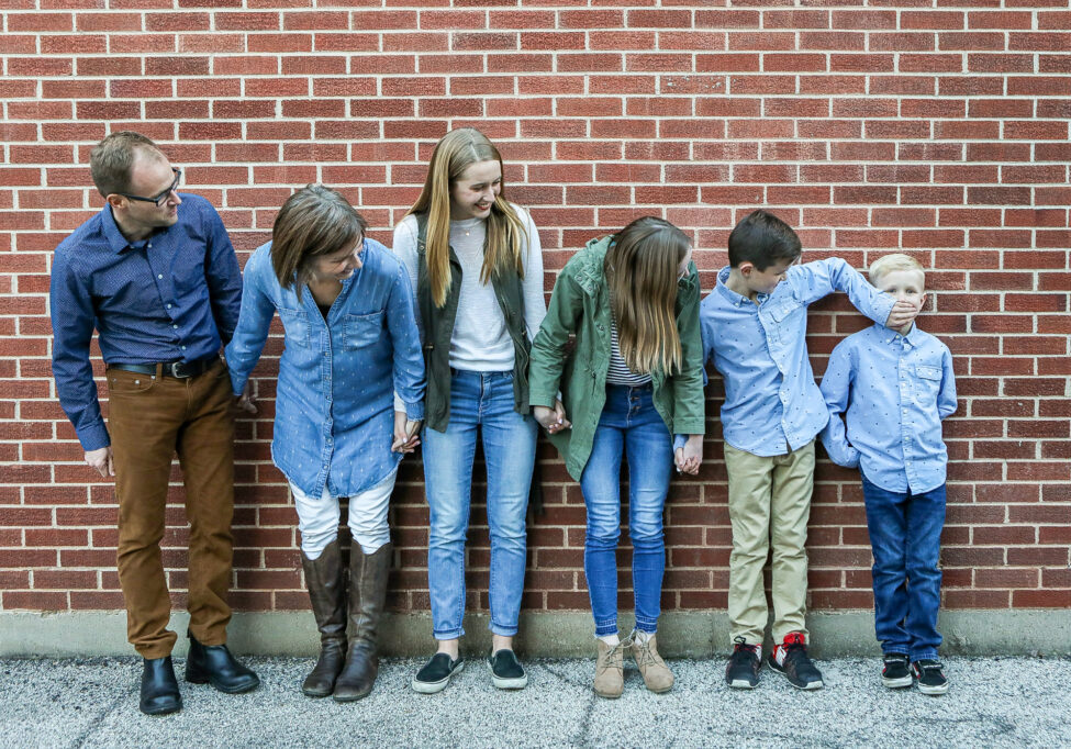 Family of 6 poses along a brick wall downtown for a photo
